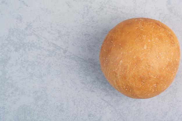 Круглая булочка с гамбургером на каменной поверхности