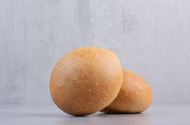 Круглые булочки для гамбургеров на каменной поверхности