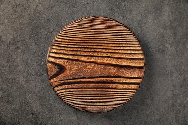 Круглая обожженная деревянная сервировочная доска на сером