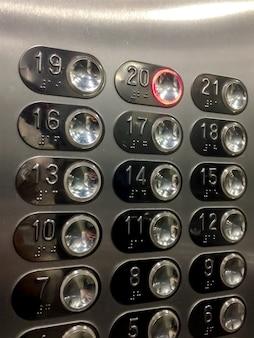 사무실 주거용 현대적인 건물에 있는 엘리베이터 내부의 둥근 버튼 제어판. 엘리베이터 패널. 건반. 20번 20번 엘리베이터 버튼을 눌렀습니다. 크롬 배경입니다. 찬란한 이미지