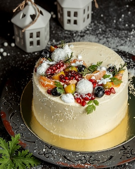 Round cake decorated with fruits and coconut sprinkles
