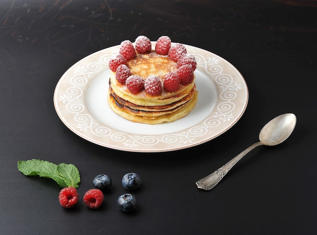 Round cake of several layers with raspberries