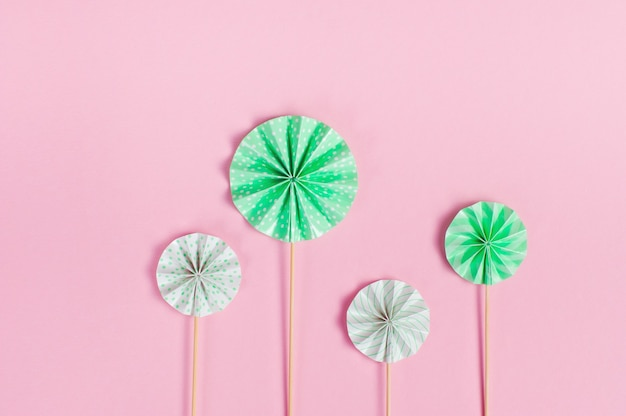 Round cake toppers on wooden sticks on pink background with blank space for text. kids party decoration concept. top view, flat lay.
