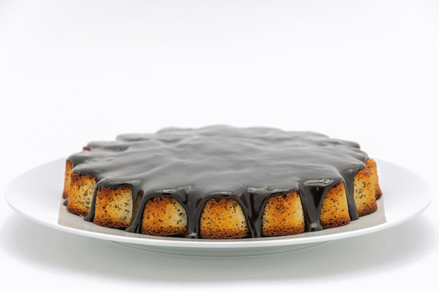 Round cake with poppy seeds covered in chocolate on a plate on a white background. isolated.