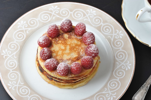 Round cake with raspberries and cup of tea