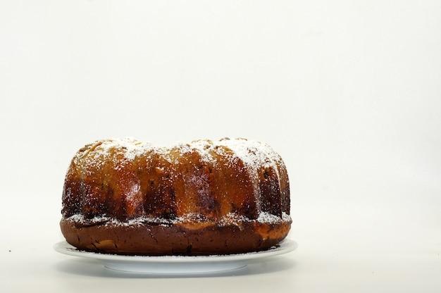 白い壁に分離された砂糖粉と丸いケーキ