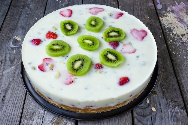Round cake of yogurt and strawberries with kiwi on a wooden table