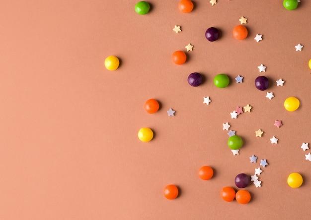 茶色の背景に異なる色の丸いお菓子