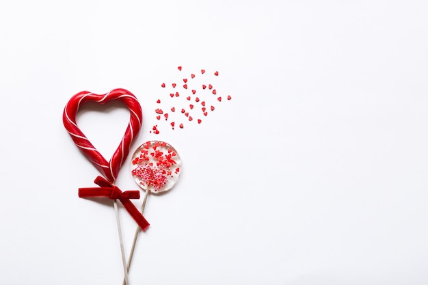 Round candy and a heart shaped lollipop symbolizing love on a white background