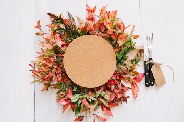 Круглый картон и столовые приборы на осенних листьях
