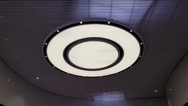 Круглый потолочный светильник на натяжной потолок в торговом центре.