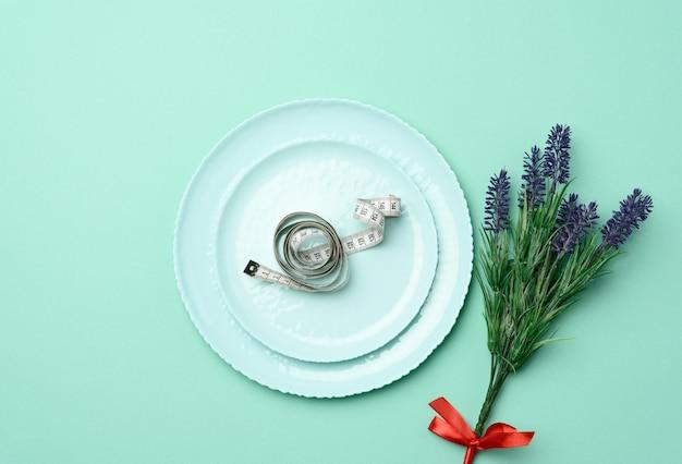 Круглая керамическая тарелка и сантиметр как концепция похудения