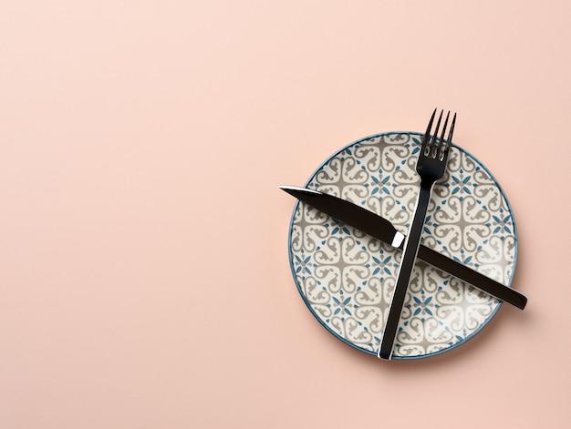 Круглая керамическая тарелка, скрещенные нож и вилка