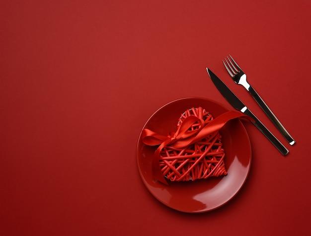 Круглая керамическая тарелка и вилка с ножом на красном фоне