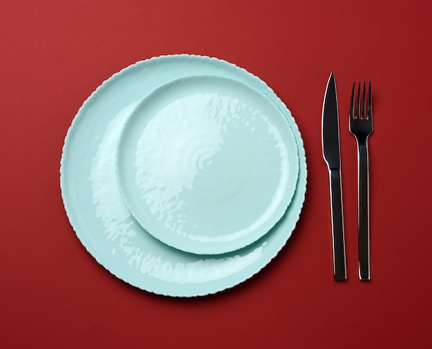 Круглые керамические тарелки, вилка с ножом на красном фоне