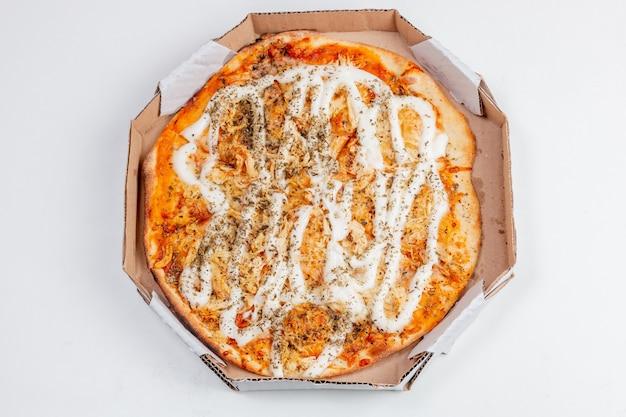 白いテーブルの上にカトゥピリチーズと丸いチキンピザ。ブラジル料理で非常に一般的な組み合わせ。