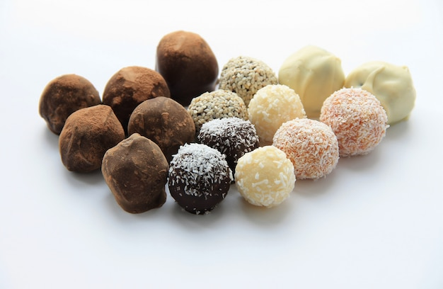 Round chocolate candies scattering on white background