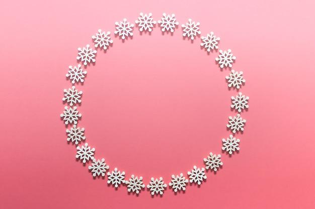 Круглый рождественский венок из белых деревянных снежинок на розовой поверхности.