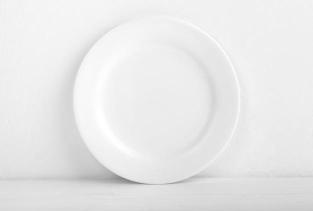 Круглая чистая тарелка, стоящая у белой стены