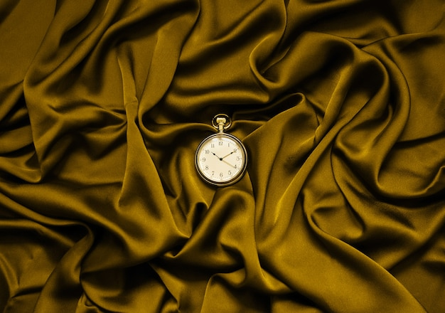 Round clock on a fabric background. fortuna gold