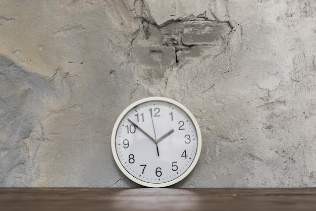 Round clock face leaning against damaged concrete wall on wooden desk