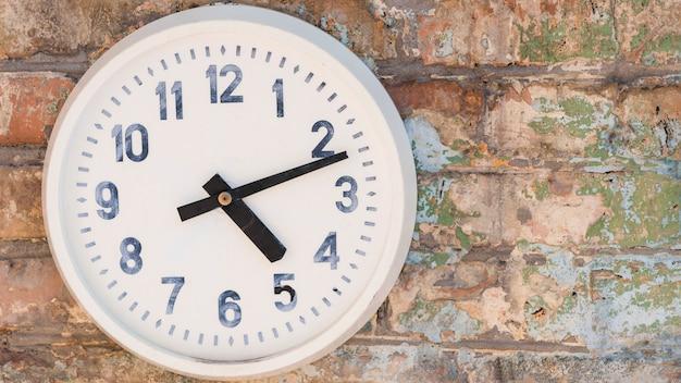Round clock hanging on weathered brick wall