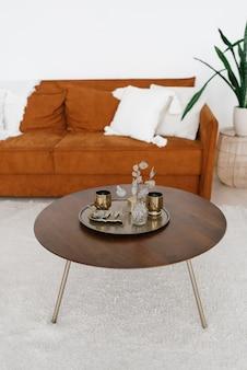 Круглый журнальный столик с подносом для стаканов, цветы в вазе в гостиной в скандинавском стиле