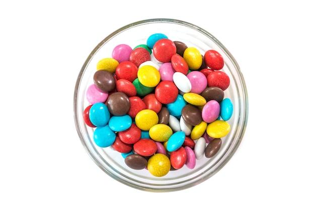 Круглые цветные конфеты в стеклянной тарелке на белом фоне. вид сверху.