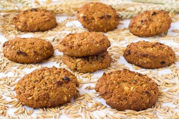 На овсяных зернах лежит круглое печенье.
