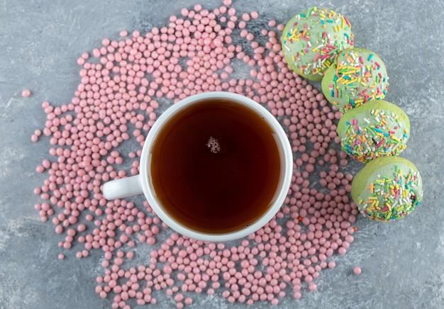Biscotti rotondi con glassa di crema verde e tazza di tè.