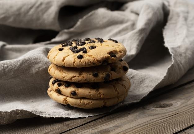 섬유 수건에 초콜릿 조각이있는 둥근 쿠키, 파이 스택