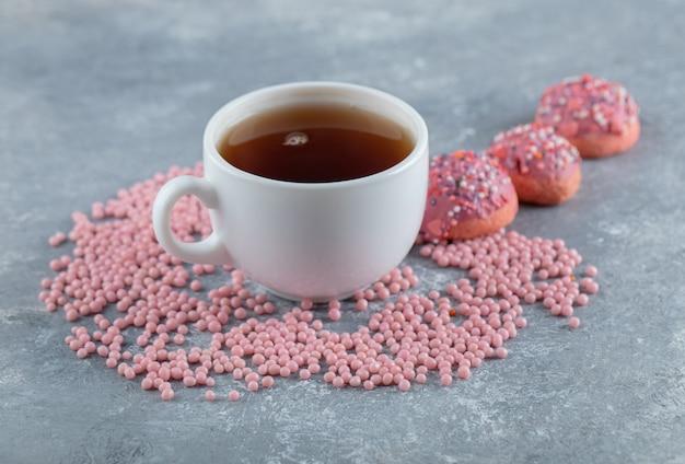 Biscotti rotondi con glassa di crema rosa e tazza di tè.