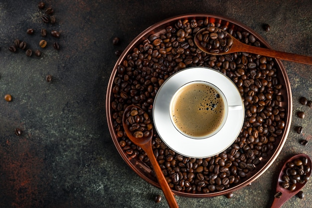 Round copper tray with kopi luwak coffee beans, wooden spoons, white cup of coffee with saucer on dark surface