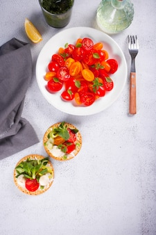 Round crispbread with greens and vegetables, fresh tomatoes salad on the dinner table. healthy food concept. top view