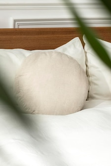 Round cushion on a bed