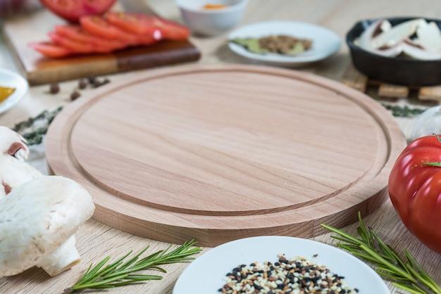 Круглая разделочная доска с пищевыми ингредиентами для приготовления кулинарных блюд