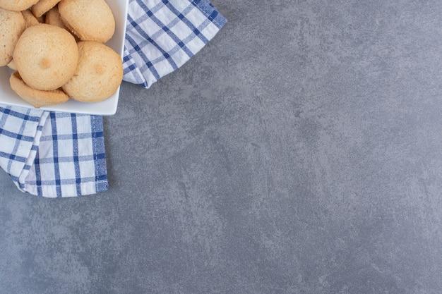 Biscotti deliziosi rotondi in ciotola bianca.
