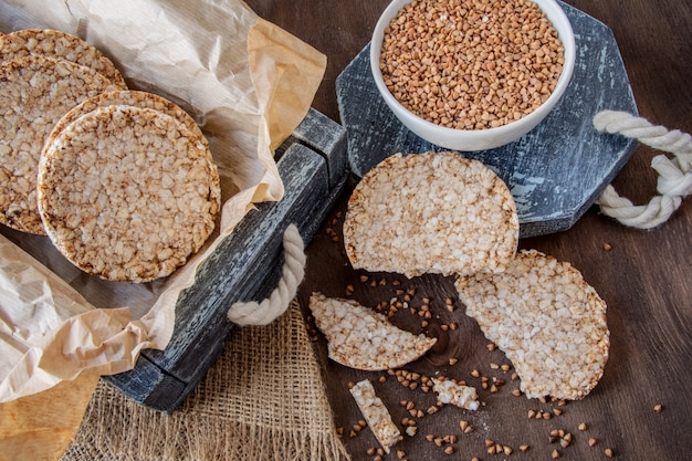 Round dietary loaves of airy buckwheat  in vintage box and a cup of raw buckwheat