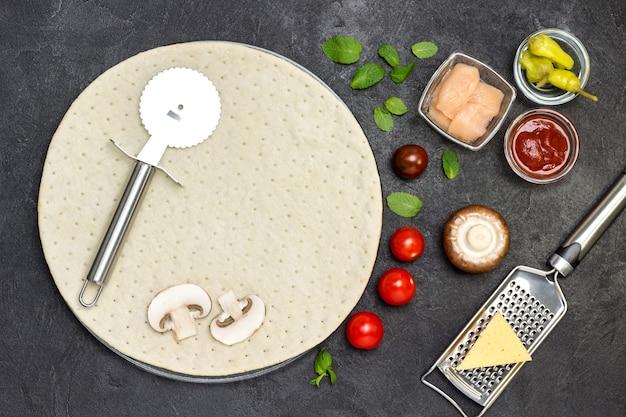 Круглая основа из теста для пиццы и различных ингредиентов