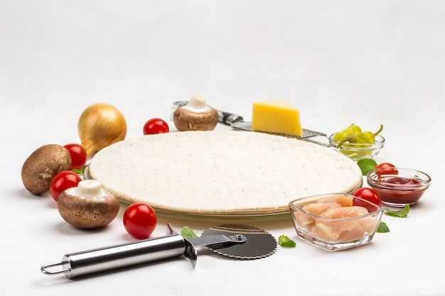 Round dough base for pizza and various ingredients