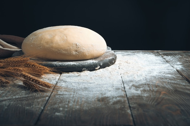 Круглое тесто на доске в муке и пшенице на темном фоне.