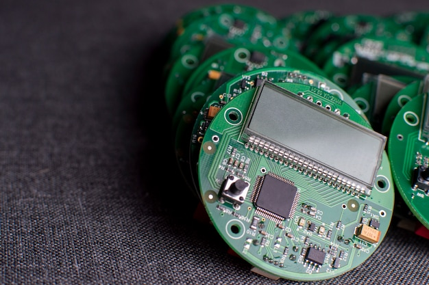 Round electronic boards with display, microchip and processor, many clock components, close-up