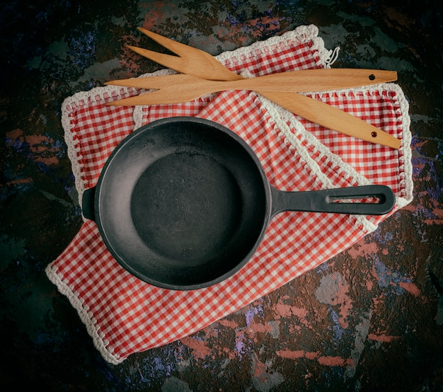 Round empty black cast-iron frying pan on a red napkin