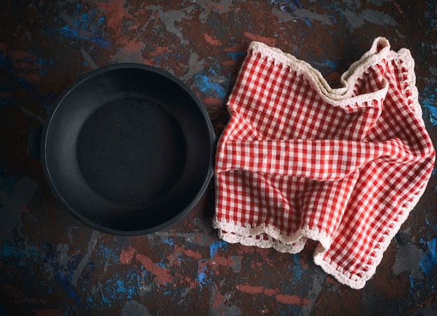 Round empty black cast-iron frying pan with a red napkin in a red box