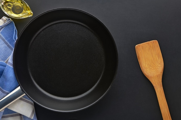 Round empty frying pan on black table background. griddle utensils for frying meat or vegetable. top view with copy space for text.