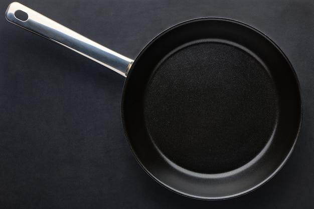 검은색 테이블 배경에 둥근 빈 프라이팬. 고기나 야채를 튀기기 위한 철판 도구. 텍스트 복사 공간이 있는 상위 뷰입니다.