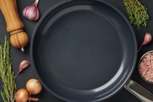 향신료와 조미료와 함께 검은 테이블 배경에 둥근 빈 프라이팬. 고기나 야채를 굽기 위한 철판 도구. 텍스트 복사 공간이 있는 상위 뷰입니다.