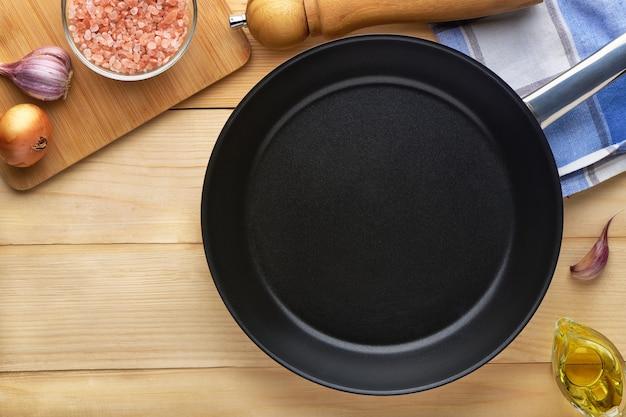 향신료와 조미료와 함께 나무 테이블에 둥근 빈 프라이팬. 고기나 야채를 튀기기 위한 철판 도구. 텍스트 복사 공간이 있는 상위 뷰입니다.