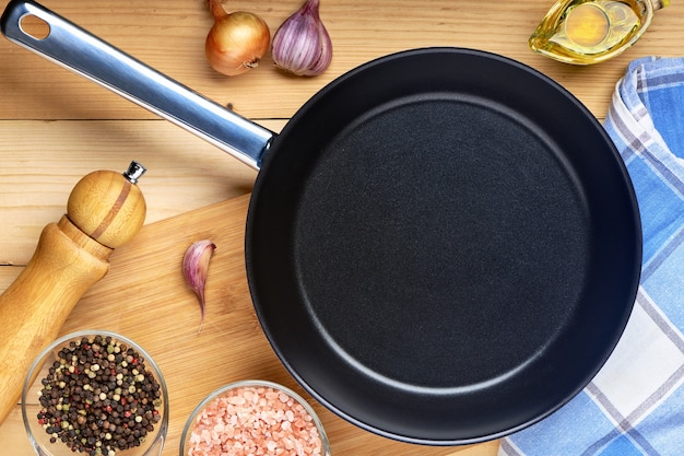 Round empty frying pan on wooden table with spices and seasoning. griddle utensils for frying meat or vegetable. top view with copy space for text.