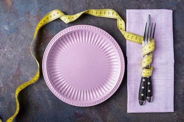 フォーク、ナイフ、黄色の測定テープで丸い空の皿